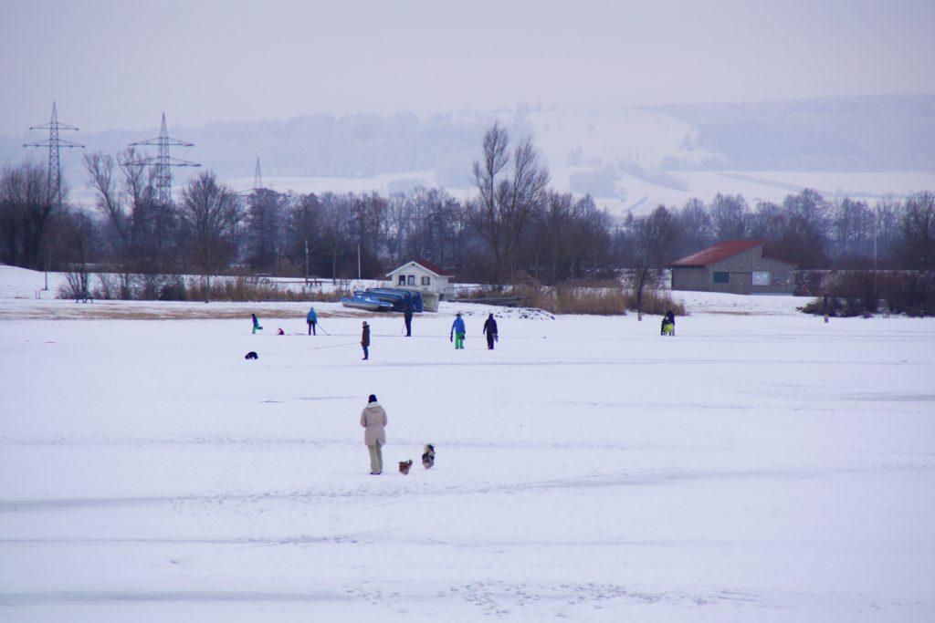 Auf dem komplett gefrorenen Altmühlsee tummeln sich die Spaziergänger